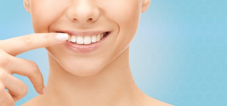 Foto de dental health, beauty, hygiene and people concept - close up of smiling woman face pointing to teeth over blue background - Imagen libre de derechos