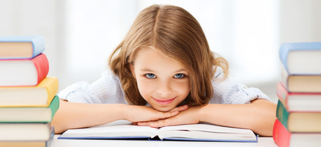 Photo pour education and school concept - smiling little student girl with many books at school - image libre de droit