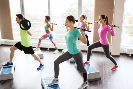 Foto de fitness, sport, training, gym and lifestyle concept - group of people exercising with barbell and bars in gym - Imagen libre de derechos