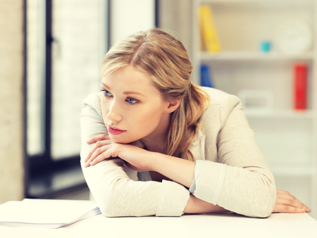 Foto de bright picture of unhappy woman in office - Imagen libre de derechos