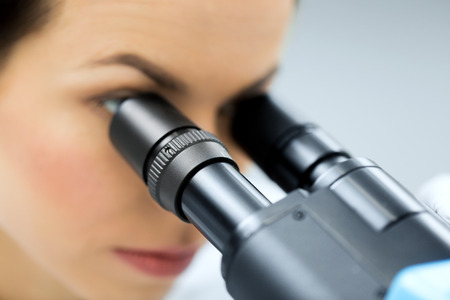 Foto de close up of young female scientist face looking to microscope eyepiece and making or research in clinical laboratory - Imagen libre de derechos