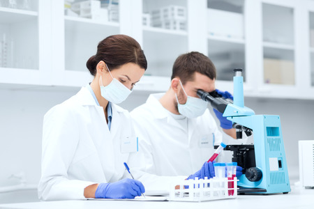 Photo for young scientists with test tube and microscope making research in clinical laboratory and taking notes - Royalty Free Image