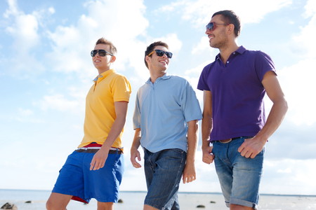 Photo pour friendship, summer vacation, holidays and people concept - group of smiling male friends in sunglasses walking along beach - image libre de droit