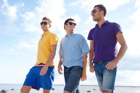 Foto de friendship, summer vacation, holidays and people concept - group of smiling male friends in sunglasses walking along beach - Imagen libre de derechos