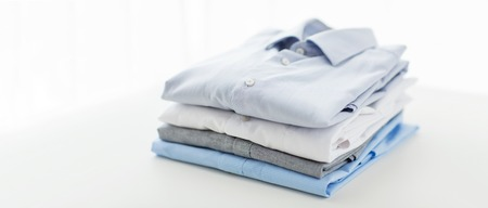 Foto de ironing, laundry, clothes, housekeeping and objects concept - close up of ironed and folded shirts on table at home - Imagen libre de derechos