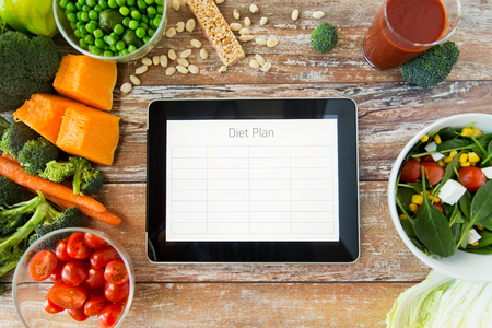 Foto de healthy eating, dieting, slimming and weigh loss concept - close up of diet plan on tablet pc screen and vegetables - Imagen libre de derechos