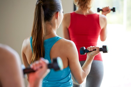 Foto de fitness, sport, training, people and lifestyle concept - close up of women working out with dumbbells and flexing muscles in gym - Imagen libre de derechos