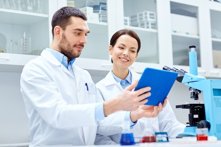 Photo pour science, chemistry, technology, biology and people concept - young scientists with tablet pc and microscope making test or research in clinical laboratory - image libre de droit