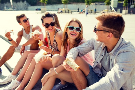 group of smiling friends in sunglasses sitting with food on city square