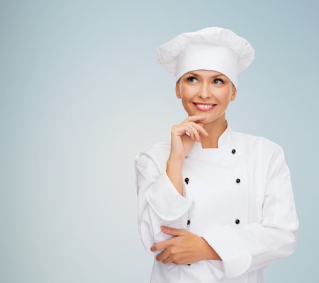 Foto für smiling female chef, cook or baker dreaming over gray background - Lizenzfreies Bild