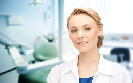 Foto per happy young female dentist with tools over medical office background - Immagine Royalty Free