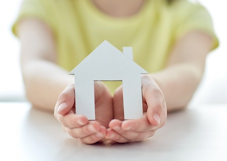 Photo for people, charity, family and home concept - close up of happy girl holding paper house cutout in cupped hands - Royalty Free Image