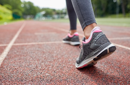 Foto de fitness, sport, training, people and lifestyle concept - close up of woman feet running on track from back - Imagen libre de derechos