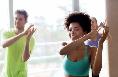 Photo pour fitness, sport, dance and lifestyle concept - group of smiling people with coach dancing zumba in gym or studio - image libre de droit