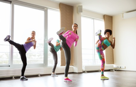 Foto de fitness, sport, training, gym and martial arts concept - group of women working out fighting technique in gym - Imagen libre de derechos
