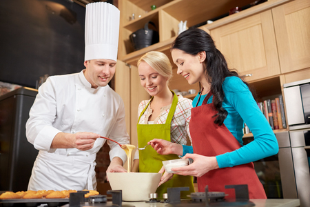 Foto per cooking class, culinary, bakery, food and people concept - happy group of women and male chef cook baking muffins in kitchen - Immagine Royalty Free