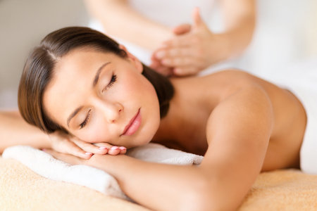 Foto de health, beauty, resort and relaxation concept - beautiful woman with closed eyes in spa salon getting massage - Imagen libre de derechos