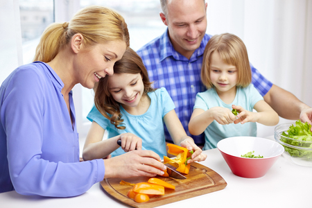 Photo pour food, children, culinary and people concept - happy family with two kids cooking vegetables at home - image libre de droit