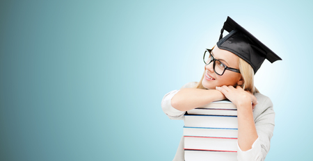 Photo for education, happiness, graduation and people concept - picture of happy student in mortar board cap with stack of books daydreaming over blue background - Royalty Free Image
