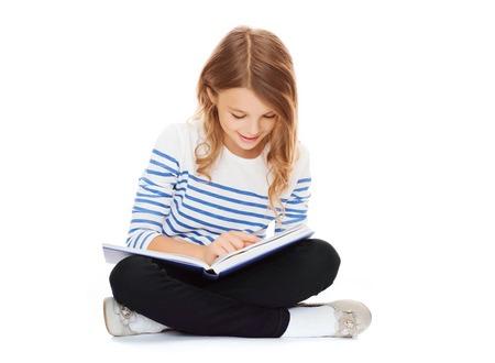 Foto de education and school concept - little student girl sitting on floor and reading book - Imagen libre de derechos