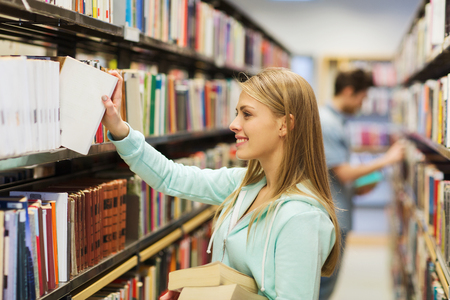 Foto de people, knowledge, education and school concept - happy student girl or young woman taking book from shelf in library - Imagen libre de derechos