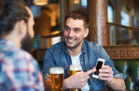 Photo pour people, men, leisure, friendship and technology concept - happy male friends with smartphone drinking beer at bar or pub - image libre de droit