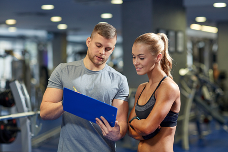 Foto de fitness, sport, exercising and diet concept - smiling young woman and personal trainer with clipboard writing exercise plan in gym - Imagen libre de derechos