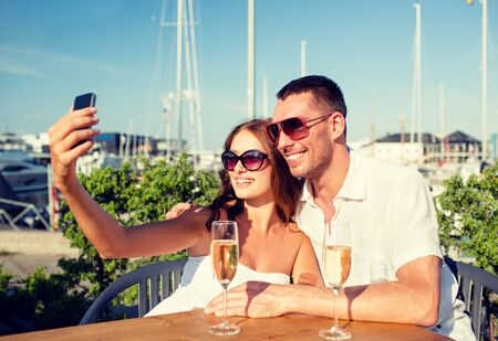 Foto de love, dating, people and holidays concept - smiling couple wearing sunglasses drinking champagne and making selfie at cafe - Imagen libre de derechos