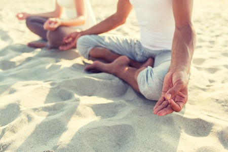 Foto de fitness, sport, people and lifestyle concept - close up of couple making yoga exercises sitting on pier outdoors - Imagen libre de derechos
