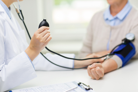 Foto de medicine, age, health care and people concept - close up of doctor with tonometer checking senior woman blood pressure level at hospital - Imagen libre de derechos