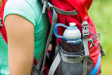 Foto de travel, tourism, hike and people concept - close up of woman with water bottle in backpack pocket - Imagen libre de derechos