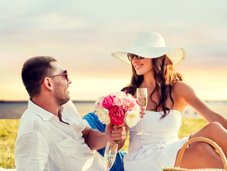 Photo pour love, dating, people and holidays concept - smiling couple drinking champagne on picnic over seaside sunset background - image libre de droit