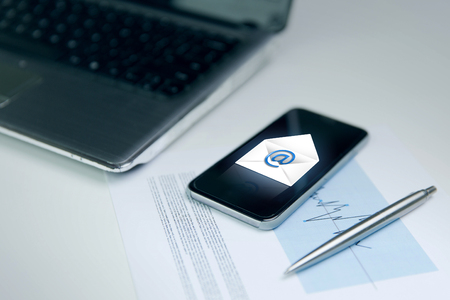 Foto de business, technology and communication concept - close up of smartphone with email message icon , laptop computer and chart with pen on office table - Imagen libre de derechos