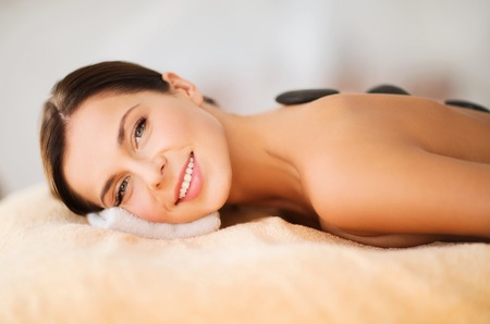 Photo for health and beauty, resort and relaxation concept - beautiful woman in spa salon with hot stones - Royalty Free Image