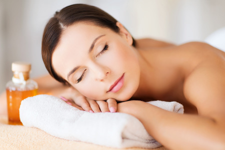 Photo for beauty and spa concept - happy woman in spa salon lying on the massage desk - Royalty Free Image