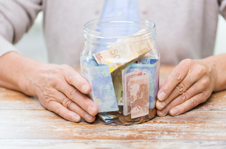 Photo for savings, money, annuity insurance, retirement and people concept - close up of senior woman hands with money in glass jar - Royalty Free Image