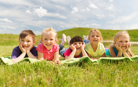Photo pour summer, childhood, leisure and people concept - group of happy kids lying on blanket or cover outdoors - image libre de droit