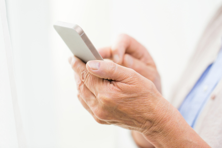 Photo pour technology, communication age and people concept - close up of senior woman hands with smartphone texting message at home - image libre de droit