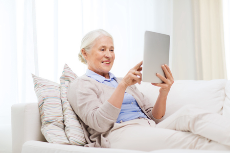 Photo pour technology, age and people concept - happy senior woman with tablet pc computer at home - image libre de droit