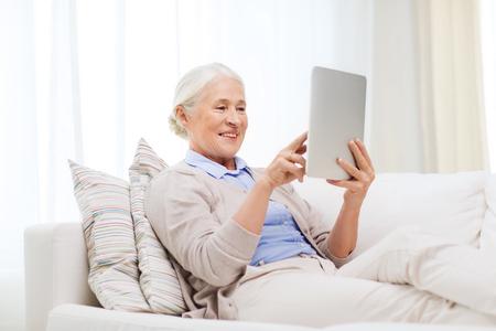 Foto de technology, age and people concept - happy senior woman with tablet pc computer at home - Imagen libre de derechos