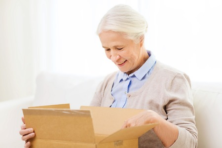 Photo pour age, delivery, mail, shipping and people concept - happy smiling senior woman looking into open parcel box at home - image libre de droit