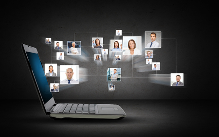 Photo pour technology, business, internet and communication concept - open laptop computer with internet contacts icons projection over dark gray background - image libre de droit