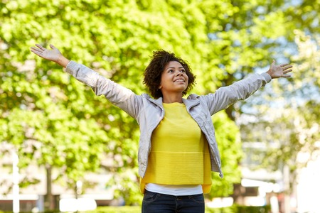 Photo pour people, race, ethnicity and portrait concept - happy african american young woman with open arms in summer park - image libre de droit