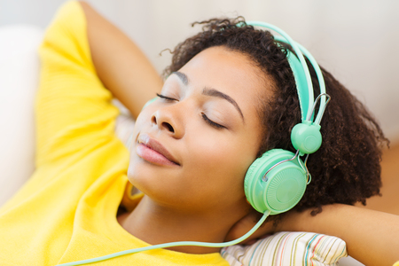 Foto de people, technology and leisure concept - happy african american young woman sitting on sofa with headphones listening to music at home - Imagen libre de derechos