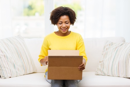 Foto de people, delivery, shipping and postal service concept - happy african american young woman opening cardboard box or parcel at home - Imagen libre de derechos