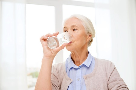 Photo pour age, health care and people concept - happy senior woman with glass of water at home - image libre de droit