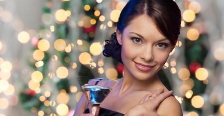 Foto de party, drinks, holidays, luxury and celebration concept - woman face with cocktail over christmas tree lights - Imagen libre de derechos