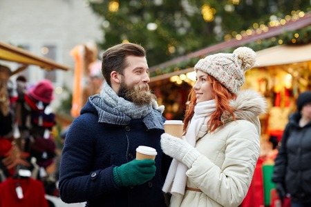 Foto de holidays, winter, christmas, hot drinks and people concept - happy couple of tourists in warm clothes drinking coffee from disposable paper cups in old town - Imagen libre de derechos
