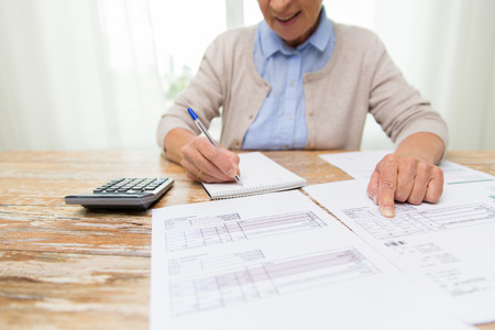 Photo pour business, savings, annuity insurance, age and people concept - close up of senior woman with papers or bills and calculator writing at home - image libre de droit