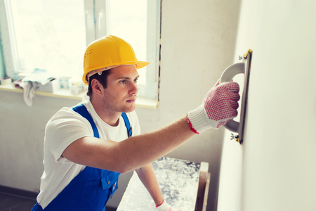 Foto per business, building, profession and people concept - builder with grinding tool indoors - Immagine Royalty Free